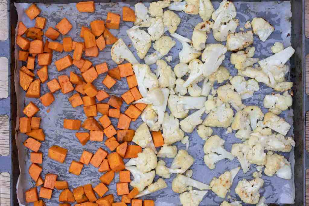 roasted sweet potato chunks and cauliflower florets on parchment-lined sheet pan