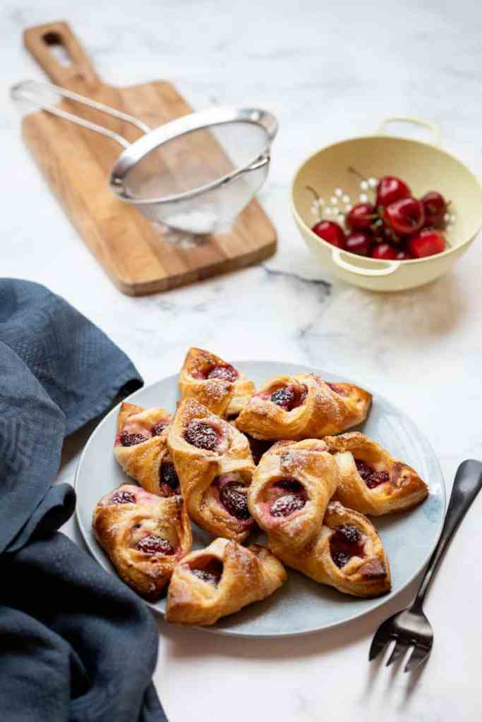 plate of cherry danishes next to fork and blue towel, with sieve and colander of cherries in background