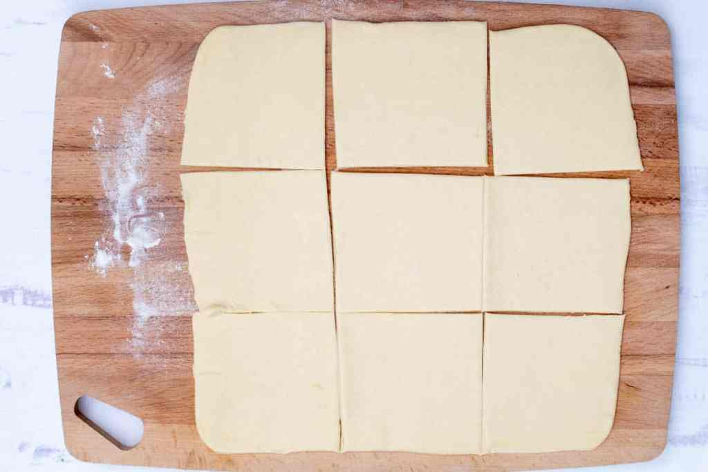 rolled out puff pastry dough on cutting board cut into 9 squares