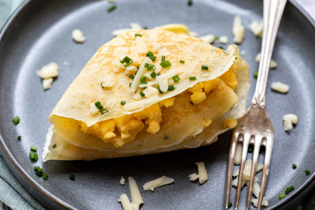close up of French crepe with egg and cheddar filling on plate with fork