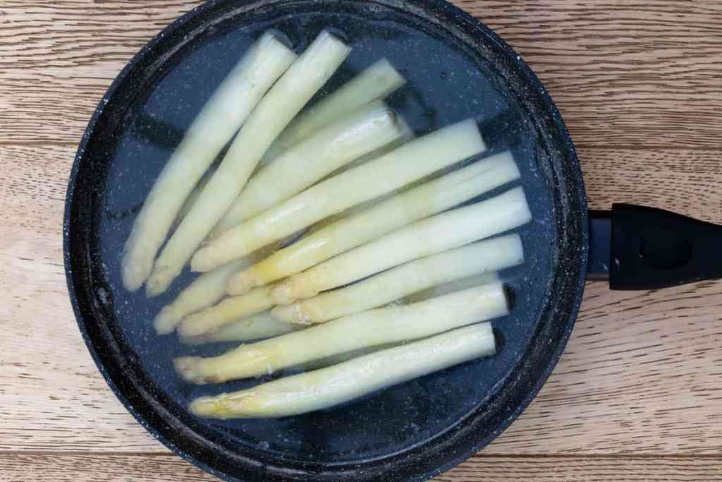 white asparagus simmering in a large saucepan of water
