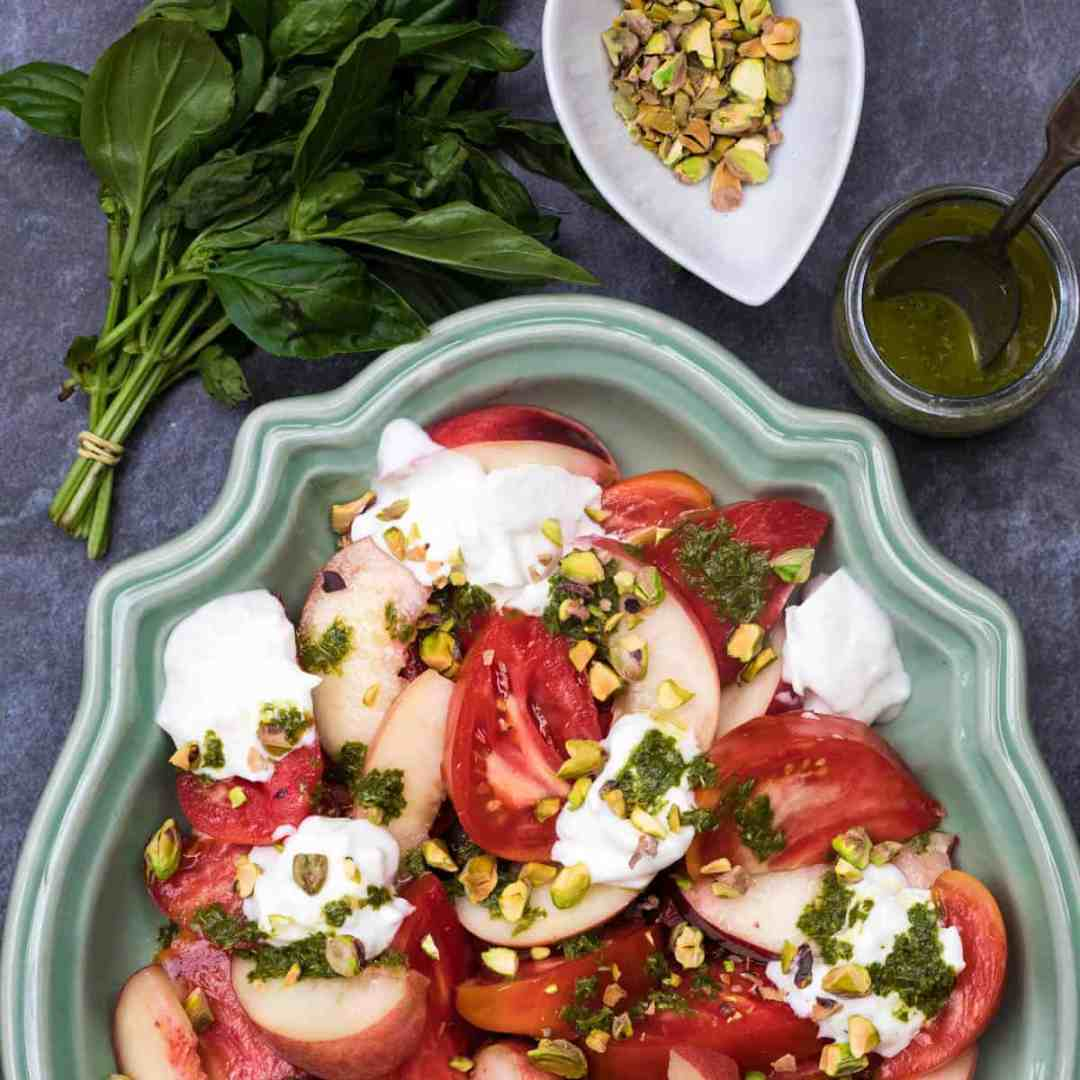 burrata caprese on green platter with basil, basil vinaigrette, and bowl of pistachios