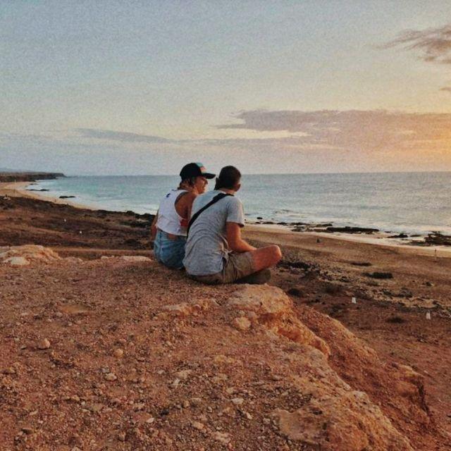 Autores del blog van salteados mirando el atardecer sentados en una playa