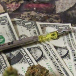 Marijuana flower and oil on top of money