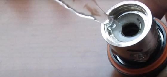 e-liquid being poured into a new vape coil -priming coils
