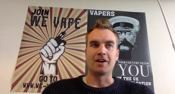 A man sits in front of a poster stating 'join we vape' featuring a hand holding a vape in it