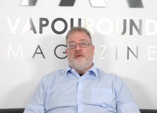 A man sits in a white room wearing a light blue shirt. A silver sign in the background reads Vapouround Magazine