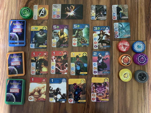 The layout for Splendor through the mobile game format. There are three rows of cards in the main area, six rows of colored tokens, and three different noble cards.