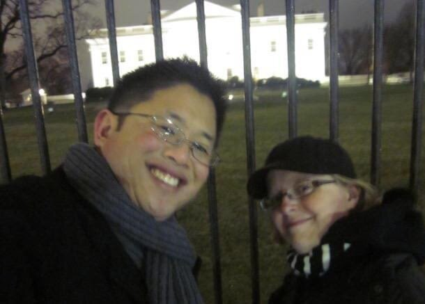 Two people in front of white house