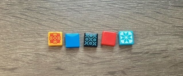 The five different Azul tiles. Each features a vibrant primary color and all but two also display an ornate pattern.