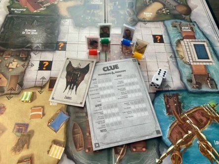 Pictured: Game cards, meeples, dice and Clue sheet are layered over a corder of the game board.