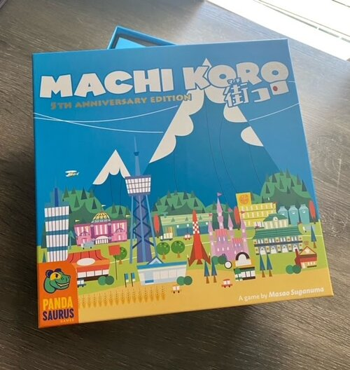 Pictured: The Machi Koro 5th Anniversary Edition game box, featuring a picturesque urban mountain sprawl. There are bright and vibrant buildings against a lush green hilly and blue mountainous backdrop.