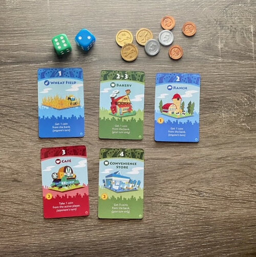 Pictured: Several game cards, including a blue Wheat Field and Ranch card, green Bakery and Convenience Store cards, and a red Cafe card. The two included dice, one green and one blue, and each of the coins, bronze single, silver five, and gold ten piece are also featured.