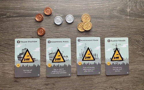 Pictured: The four grey special buildings: Train Station, Shopping Mall, Amusement Park, and Radio Tower. Also featured are the single copper, silver five, and gold ten piece coins.
