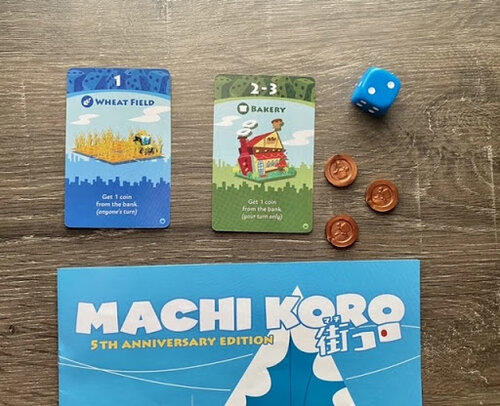Pictured: The top of the Machi Koro game box, with game cards, coins, and a blue six sided die. The coins are single coin pieces in a bronze color, the cards are the green bakery card, and blue wheat field card.