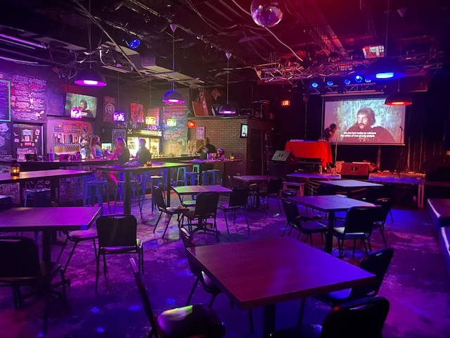 Pictured: The inside of The Geek Easy. Stage and screen in back right, bar on left side. Empty tables, chairs and stools.