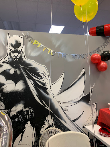 Wall with a cut out of batman on it with a silver and gold happy tenth anniversary sign