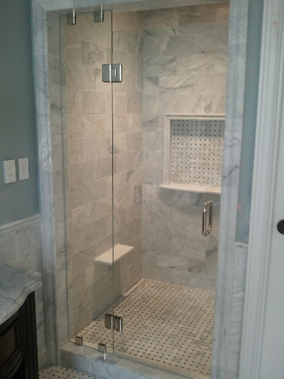 THIS FRAMELESS SHOWER DOOR WAS INSTALLED IN THE JEFFERSON HOTEL, RICHMOND VA.   UNLIKE MOST OF OUR DOORS THAT HINGE OFF A WALL, THIS DOOR HINGES OFF A  STATIONARY PANEL.  FOR SUPPORT WE SECURED THE STATIONARY PANEL TO THE CURB &  SOFFIT.
