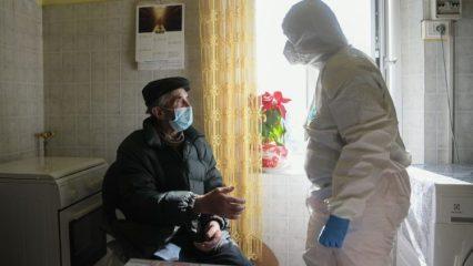 A nurse in PPE assisting an elderly man