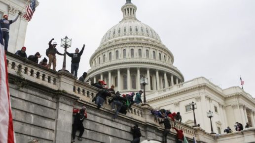 Supporters of President Trump climb on walls at the US Capitol on 6 January 2021