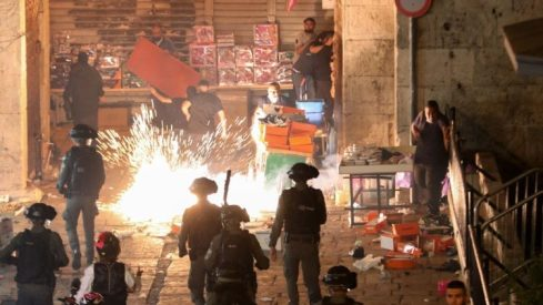 Israeli security forces fire a stun grenade at Palestinian protesters