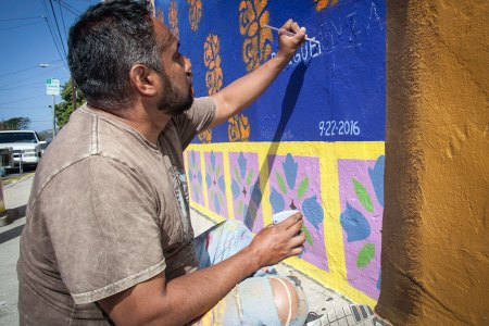 MB Hanrahan, Rolando Sigüenza and Uriel Leon with the finished mural at Harrison and Ventura Avenue. Photo by T Christian Gapen ArtWalk 2016 Global Artist of Distinction An interview with Rolando Sigüenza ArtWalk Ventura is fortunate to have the talented Oaxacan artist Rolando Sigüenza as this year's Global Artist of Distinction. Part of the folkloric art movement, his colorful paintings showcase angels, trees, animals and children, revealing a world full of hope, joy and spirituality. He took time out from his work on Oaxaca to Ventura, the mural he designed with MB Hanrahan and Uriel Leon, to answer a few questions for the VCReporter. Welcome to Ventura! How do you like it here so far?  I love the ambience! It is quite special: the fresh air and close to the sea. It is a place to enjoy, and most of all I feel great surrounded by kind and caring people. Also there's so much art to enjoy! Everywhere I go, it seems like a giant museum. Are you enjoying being a part of our ArtWalk?  I´m very humble about it. As a deaf person, many doors have been closed in the past or I've been invited only for exhibits designated for deaf people. Please don't misunderstand what I'm saying: The deaf community is my family and I'm proud to say I have friends all over the world. But I have faced [preconceived notions] from some about disabilities. This is an opportunity to distinguish myself as a person and artist in such an important venue. This recognition is not only mine — it is for all the artists in Mexico, especially from Oaxaca, the Rufino Tamayo Art School, museums and galleries. Talented and well-known artists could have been in my place right now. I'm honored, but mostly grateful. Can you tell us a little bit about your design for the mural?  Believe me it was a hard task, considering that for the first time I'm involved in a mural project. Many ideas went through my mind. The mural has a woman holding the moon and a man holding the sun. It is my invitation to mankind to thank what nature is giving us. The entire universe is our home, everything has a place to create balance and harmony in our lives. I also wanted to add a butterfly — such a small creature migrating every year through California to its final destination in Mexico, no passport needed, restrictions do not apply. There is a bird spreading its wings as a symbol of freedom. I love dogs. In many of my works, dogs have a special place. The trees embrace my idea about love. . . . They provide shelter, shade and do not set conditions to be generous. That's what love means to me. What was your inspiration?  Once my feet sensed Ventura it all came easier. I understood the spirit of this county. I'm convinced that inspiration arrives once the ambience is read in our minds. Then I know what to do and the elements to integrate. Every artist has constant traces or symbols unique to their own style, so I added elements that can easily be found on my paintings, but made them specifically to fit in Ventura. I did not have a religious education because there were no sign-language instructors when I was a kid, but my family would take me to visit churches. There was no one to explain what the priest said, so I would look around and discover the walls and wood carvings filled with angels, in different posturesIt was like they wanted to talk to me, so they became my imaginary friends, and very often are an essential part in my paintings. Any final thoughts on your experiences here?  All the comments we have received are very encouraging and motivate me to give my best. Above all, working with MB Hanrahan and Uriel Leon is already my reward. I may add that when people approach, I explain to them that I am deaf. Then magic happens and communication flows naturally. I´m taking these moments into my heart. Oaxaca to Ventura can be seen at the corner of Ventura and Harrison Avenues in Ventura. An exhibit featuring the work of Rolando Sigüenza and other Oaxacan artists will also be on display Oct. 1-28 at Bell Arts Factory, 432 N. Ventura Ave., Ventura. For more information, visit www.vitaartcenter.com or www.artwalkventura.org.