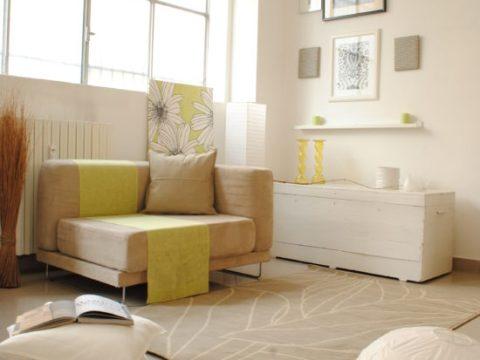 divano angolare beige con coperta e accessori verde acido