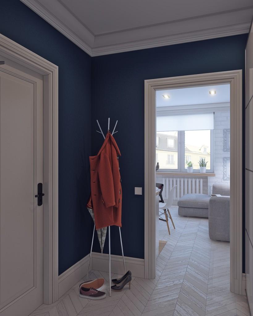 ingresso con pareti blu oltremare, porte con stipiti con decoro classico e appendiabiti da terra. Parquet a spina ungherese