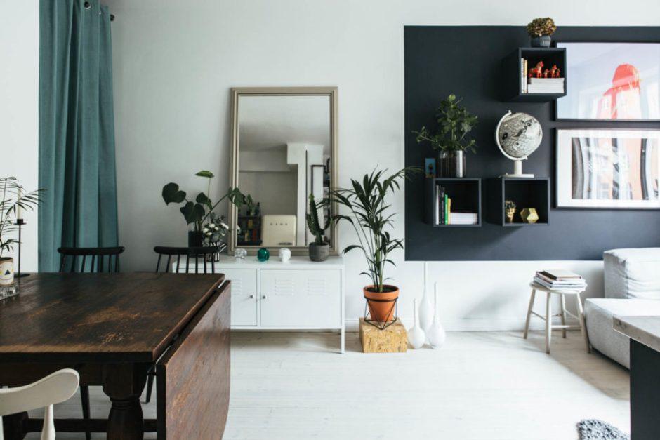 credenza bianca con specchio appoggiato sopra per organizzare una casa piccola
