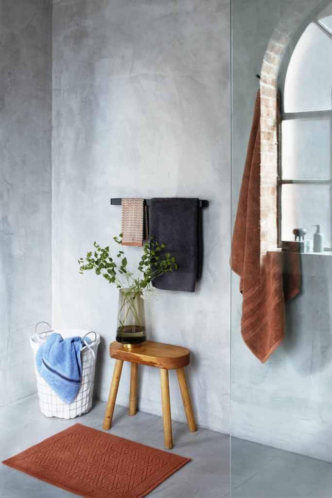 bagno con pareti in cemento ed accessori tessili in rosso mattone con cesto porta asciugamani e piccolo sgabello in legno massello.