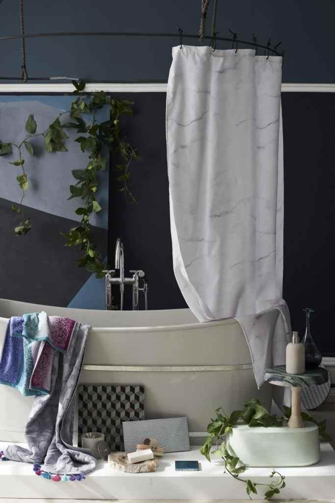 vasca freestanding con tenda effetto marmo e accessori da bagno a terra con parete di fondo grigio antracite.