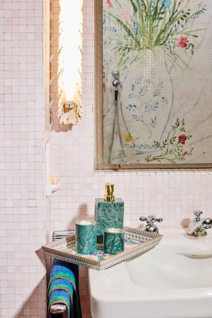 Dettaglio di lavandino da appoggio con mosaico bianco ed accessori in marmo verde acquamarina in un bagno anni '50.