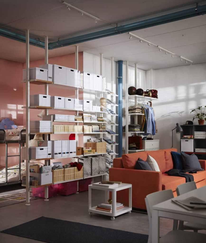 Libreria autoportante con montanti in acciaio che divide il soggiorno dalla zona notte in un open space.