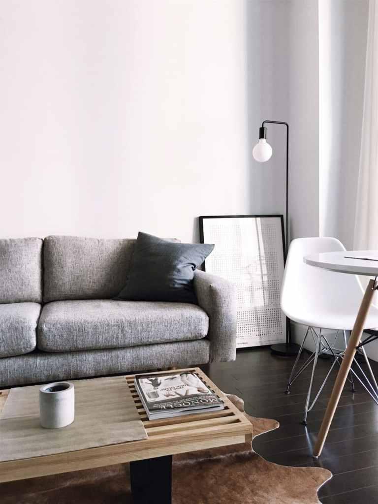 Divano a tre posti grigio con tavolino da caffè contemporaneo in legno e angolo di tavolo da pranzo rotondo con sedia Eames, illuminati da lampada da terra nordica.