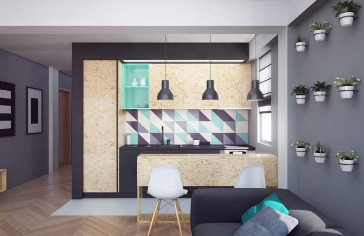 Vista frontale di una cucina lineare in osb in un piccolo appartamento, con basi laccate nere come la parete di fondo e con paraschizzi a decoro triangolare.