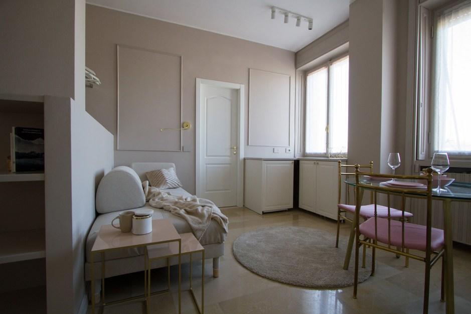 Illuminazione nelle micro case: sala da pranzo e cucina di una piccola casa nei toni del rosa e dell'oro