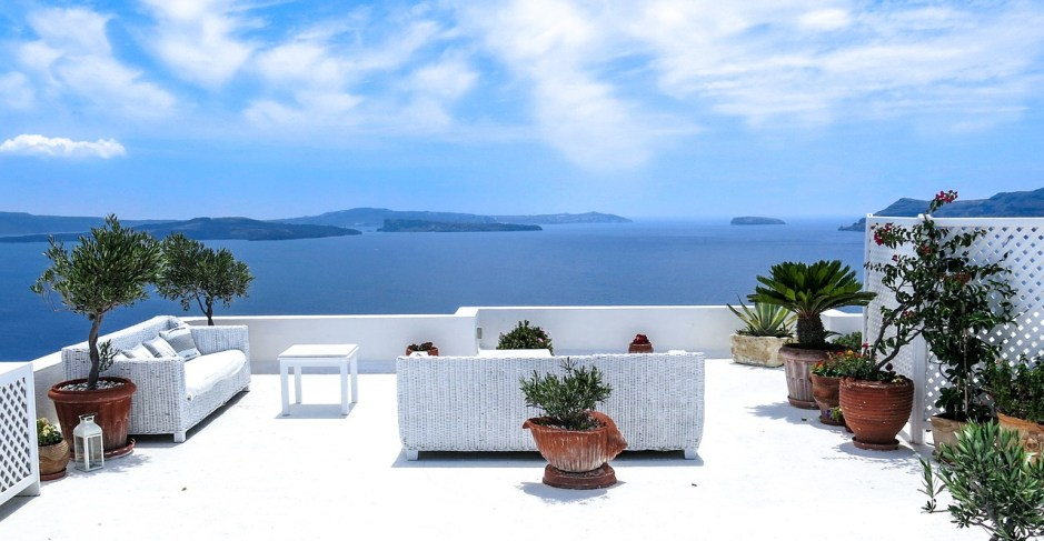 Arredare una terrazza scoperta con vista sul mare greco, con divani bianchi e ulivi