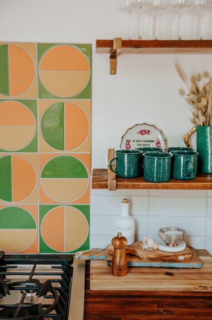 dettaglio paraschizzi cucina con piastrelle verdi e arancioni e tazze blu su una mensola