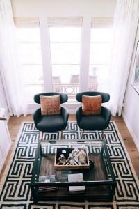 vista dall'alto di soggiorno moderno con tappeto bianco e nero, tavolo in vetro e poltrone nere