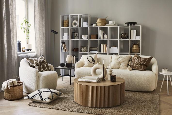 soggiorno in colori neutri con divano tessile bianco e poltrona a fianco. tavolo basso in legno di bambù e libreria bianca sul fondo