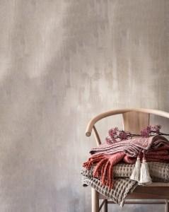 Parete in cemento sul fondo con sedia in legno nell'angolo e coperte rosa sopra