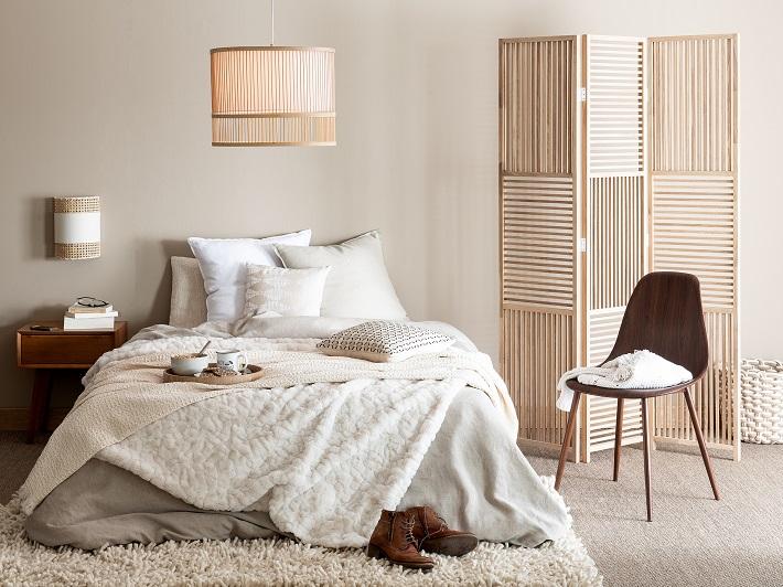 camera da letto in colori neutri con paravento in legno e sedia in palissandro