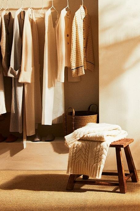dettaglio di cabina armadio con vestiti appesi e sgabello in legno