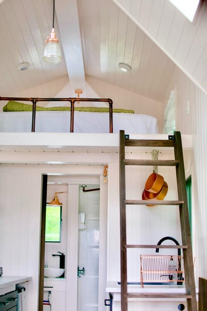letto su soppalco in legno bianco con scala in legno e bagno al piano inferiore