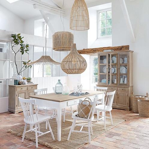 stile boho chic in casa in una sala da pranzo nei toni del bianco e del beige con lampade in rattan
