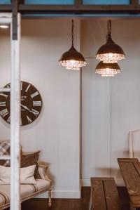 Materiali ecosostenibili per il design con scala in legno, orologio in legno e lampadario a goccia