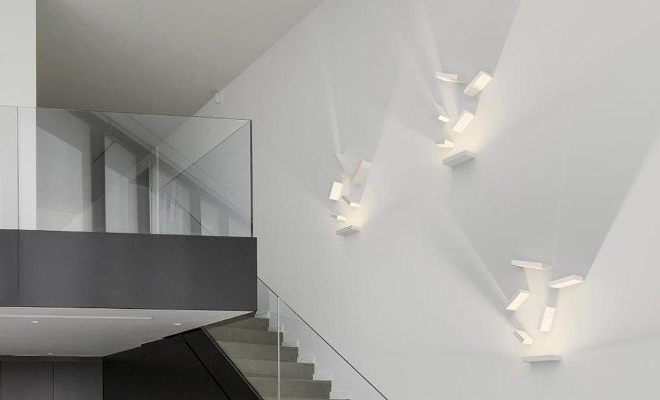 lampada da parete bianca su spazio loft con scala e parapetto vetrato