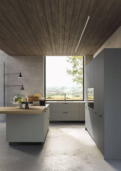 Cucina con isola in grigio chiaro, top in Okite e lavandino sotto finestra in loft