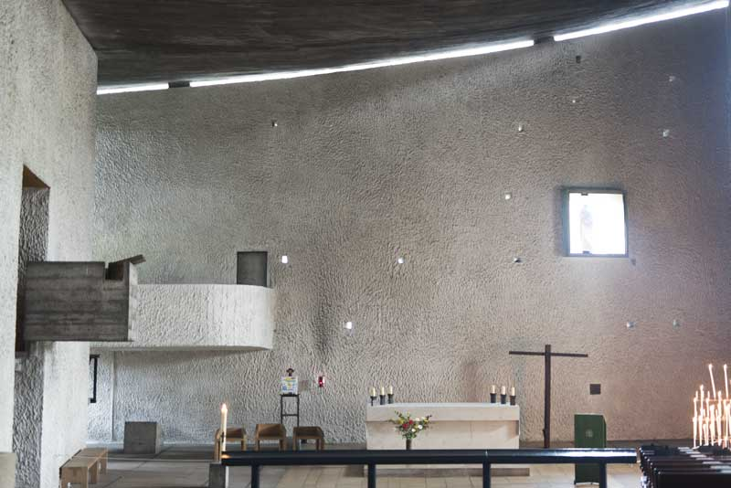 the simple, contemplative interior space of La Ronchamp chapel