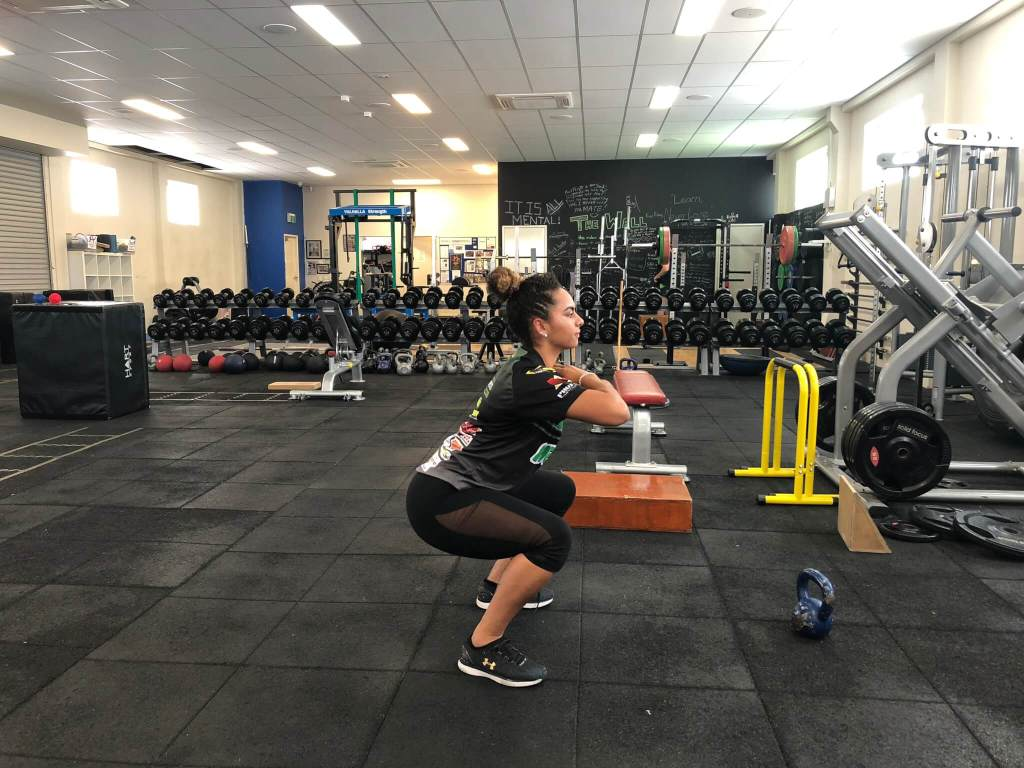 Rachel Warcon demonstrating bodyweight squat technique at Vector Health